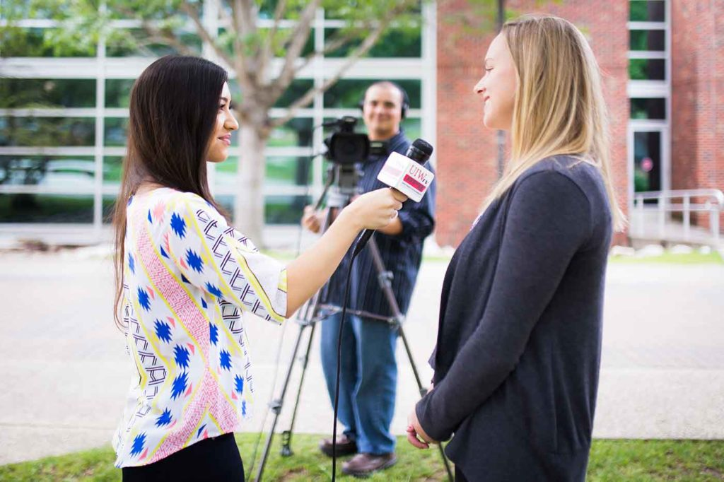 UIWtv reporter conducts interview on campus.